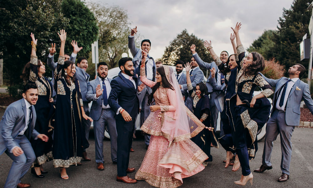 Indian groom dressed in traditional black suit and pretty bride in pink wedding dress with golden embroidery dance before a car together with their cheerful groomsman and bridesmaids