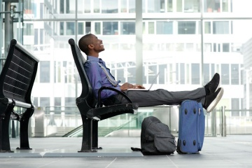 Side portrait of smiling young businessman sitting with laptop and luggage at airport
