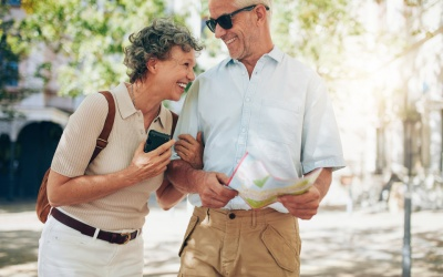 Smiling mature man and woman roaming around the city.