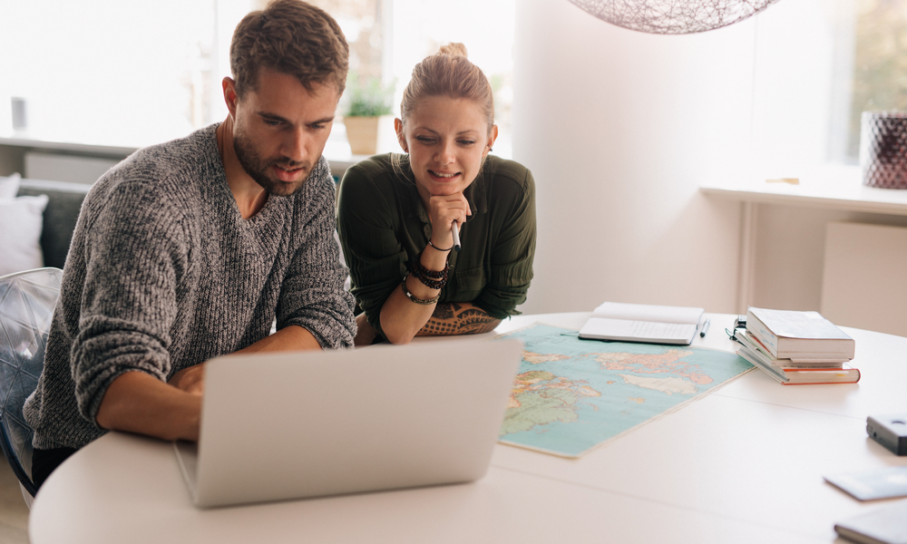Young man and woman sitting with world map and computer on study table.