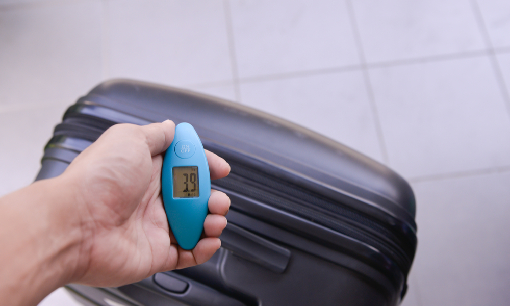 Man hand is using digital weight scale to weigh the luggage