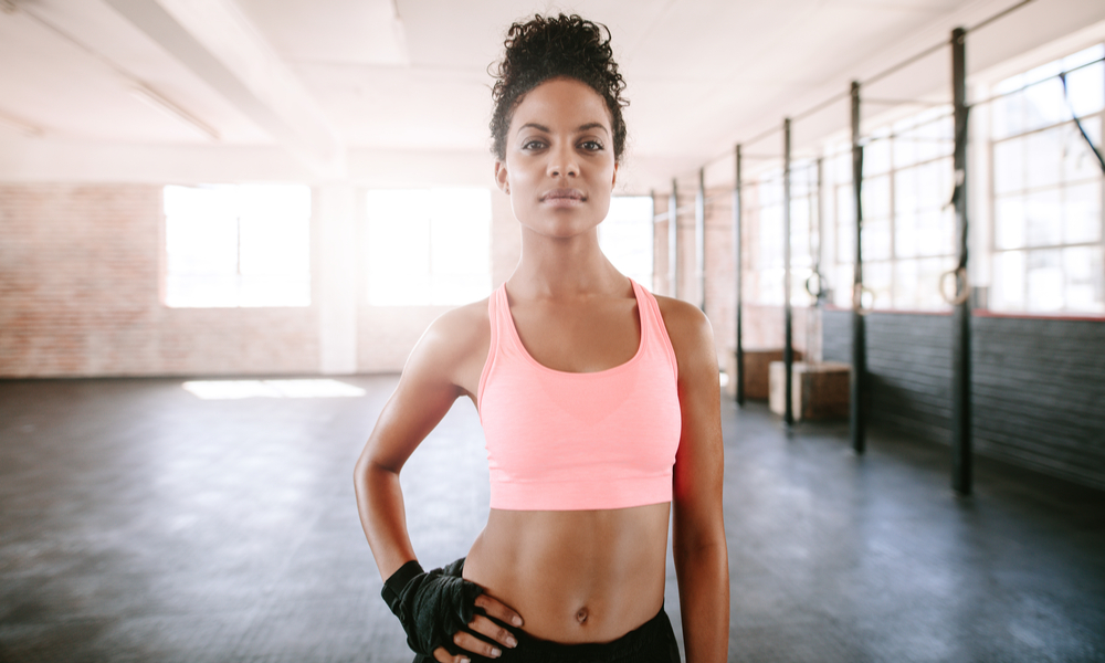 Portrait of confident young woman standing in gym.