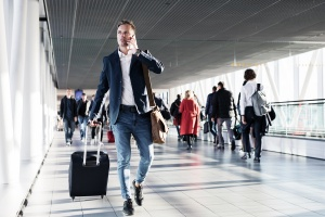 Busy man speaking on phone and walking in airport