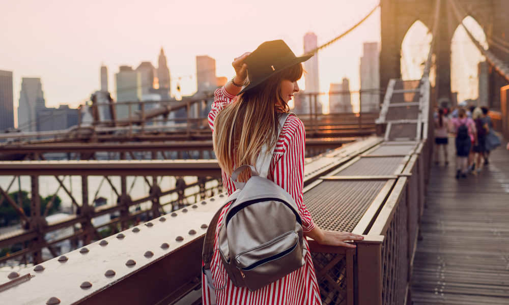 View from back of traveling woman in red dress, stylish black hat and silver bag pack enjoying amazing view from Brooklyn bridge in New York.