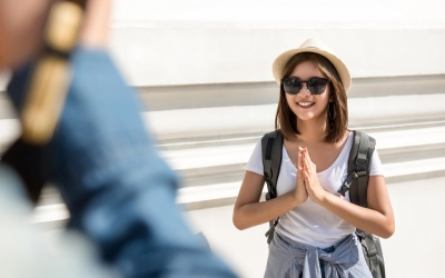 Asian female tourist backpacker acting Wai, Thai greeting, while traveling in Bangkok Thailand on summer holidays