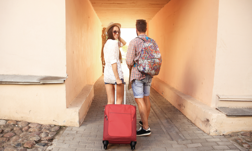 two travelers walking with a suitcase