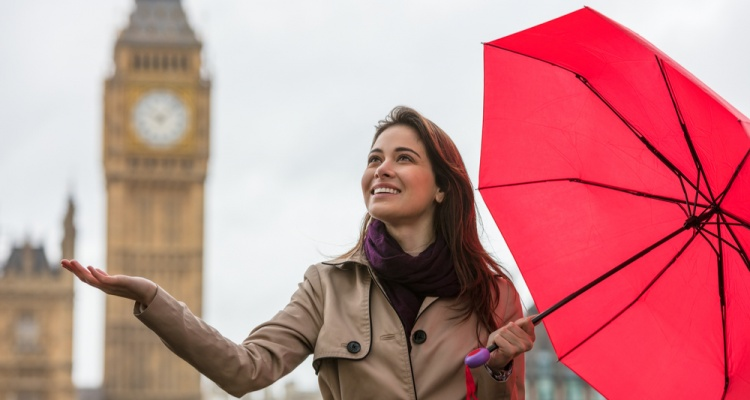 young woman with a red umbrella, hand out, checking for rain by Big Ben, London, England