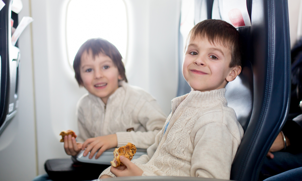 Two children, eating sandwiches on board in aricraft