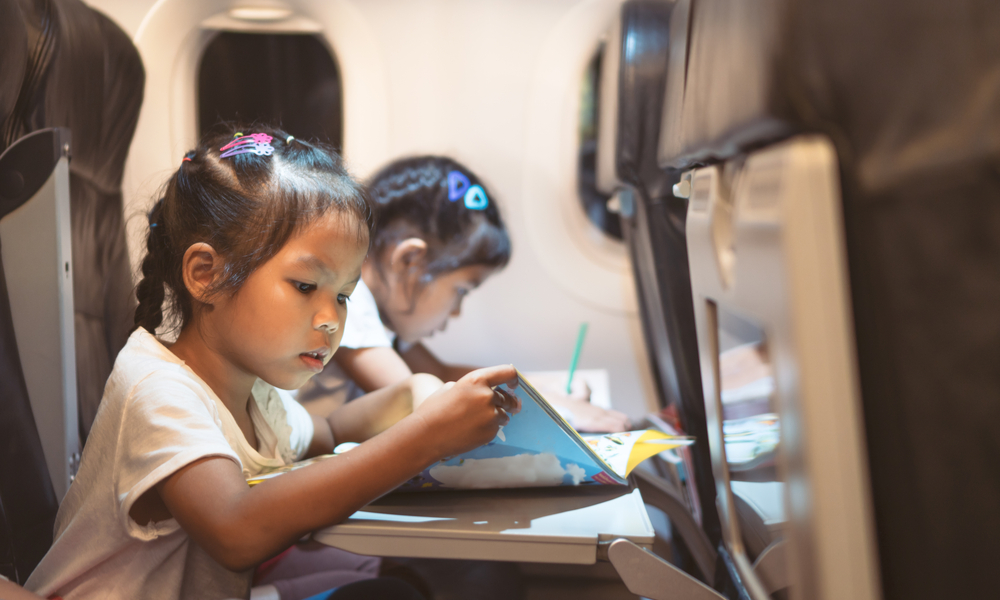 girls traveling by an airplane and spending time by drawing and reading a book during the flight