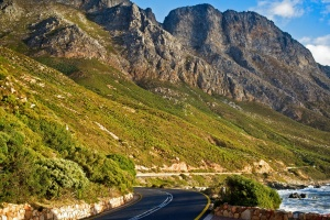 The green and rocky hilly slopes along the beautiful and scenic coastal road of the Garden Route, Cape Town, South Africa.