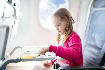 Kid in air plane sitting in window seat