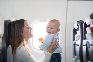 Young mom, playing and breastfeeding her toddler boy on board of aircraft,