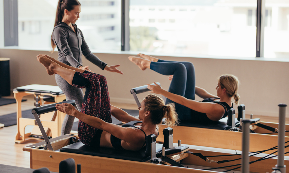 Women doing pilates exercises lying on pilates workout machines while their trainer guides them