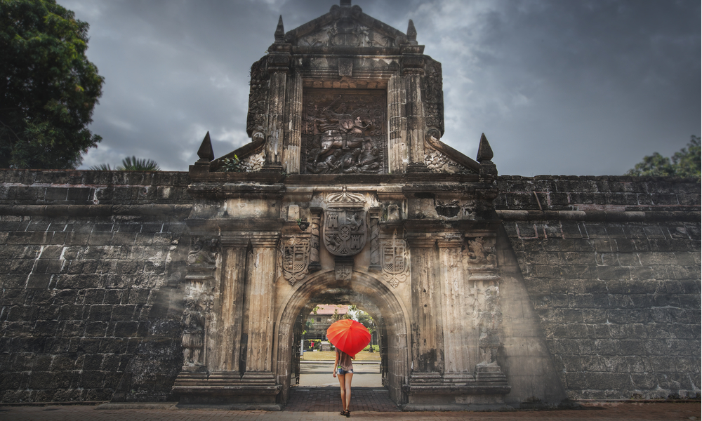 Woman with red umbrella stay at entrance gate in Fort Santiago, Intramuros city in Manila, Philippines