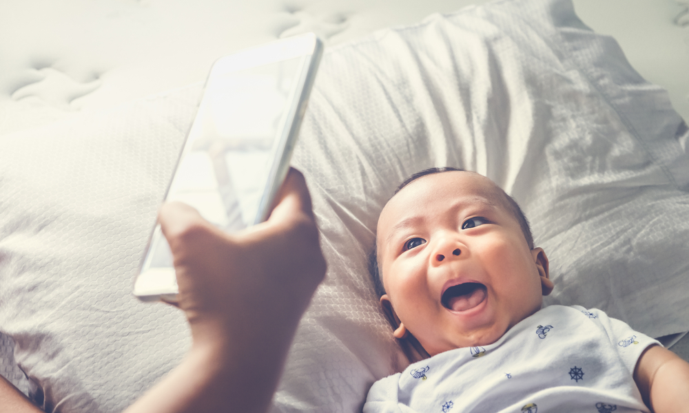 igh angle shot of happy mother taking picture her baby boy in bed with smart phone at home.