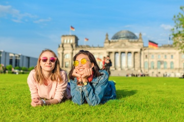 Two Young happy girls wearing sun glasses lying on a grass and have fun in front of the Bundestag building in Berlin