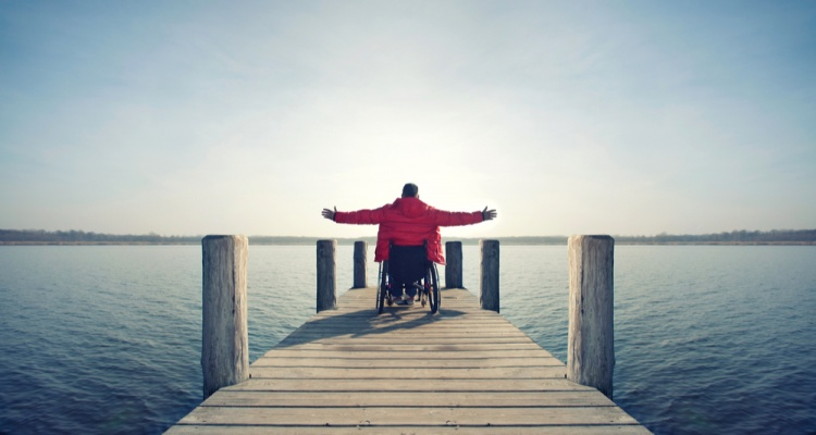 young man in wheelchair with wide opened arms enjoying his life at a lake in spring