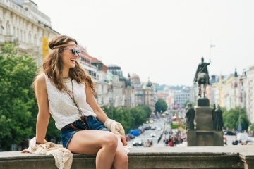 Happy young woman tourist in boho chic clothes relaxing on parapet in the historical center of Prague