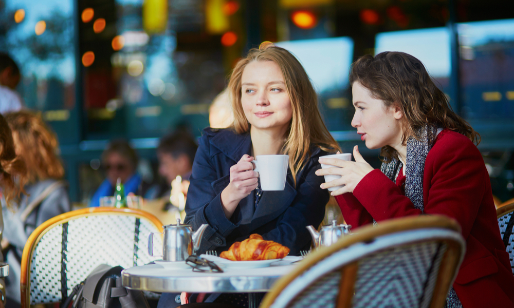 Two young girls in Parisian outdoor cafe, drinking coffee with croissant and chatting.