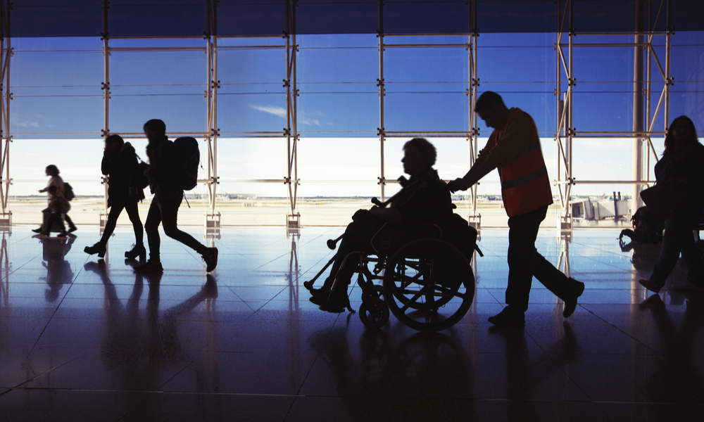 Silhouette of man in wheelchair and people carrying luggage and walking in airport
