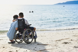 boy in a wheelchair on the beach with his arm around a boy