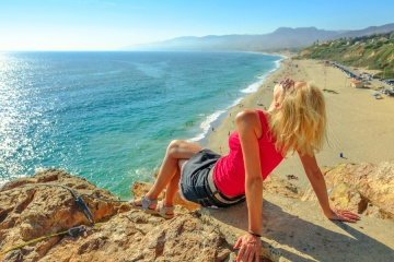 Caucasian female looks Point Dume State Beach from Point Dume promontory on Malibu coast in CA, United States