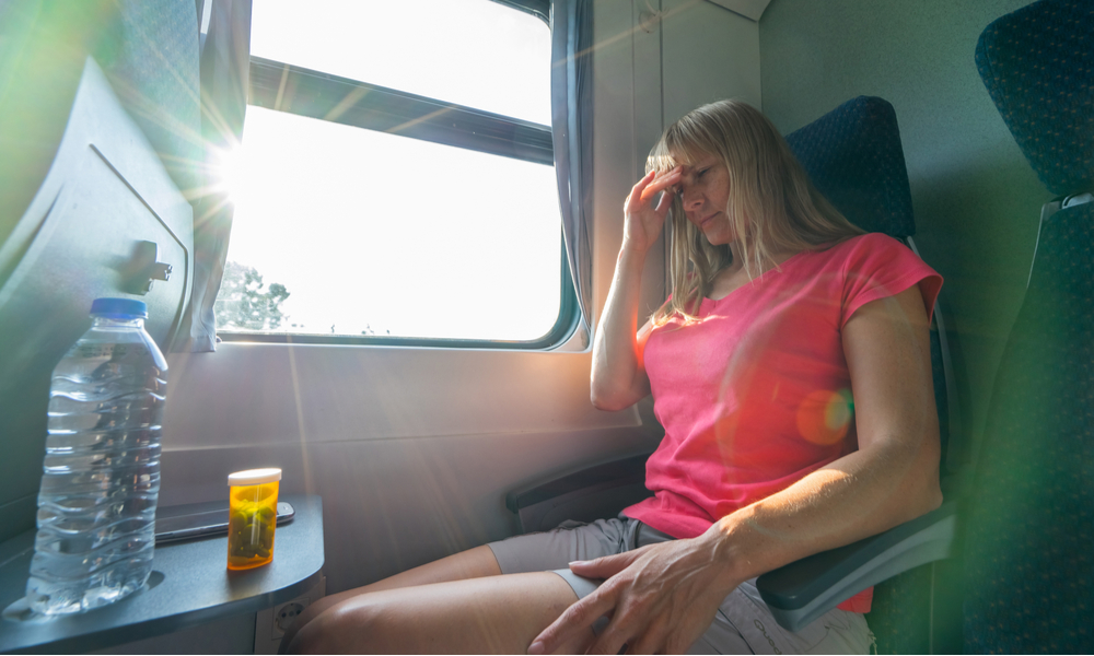 Stressed and tired young woman sitting near the window and with bottle of water and tablets on table while travelling by train.