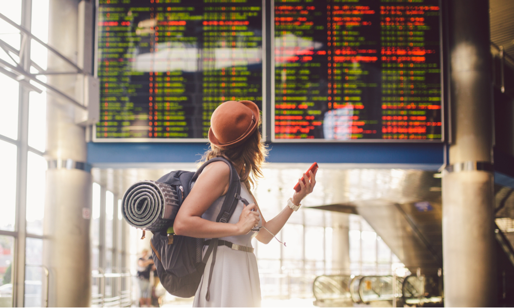 Beautiful young caucasian woman in dress and backpack standing inside train station or terminal looking at a schedule holding a red phone