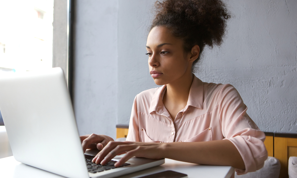 Close up portrait of a young woman working on laptop