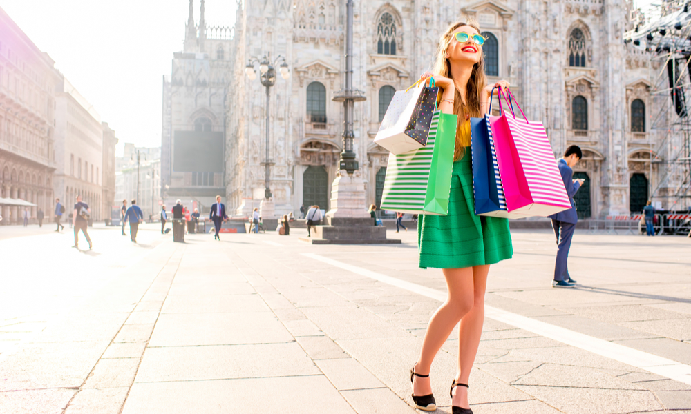 Young woman standing with colorful shopping bags on the main square in front of the famous duomo cathedral in Milan