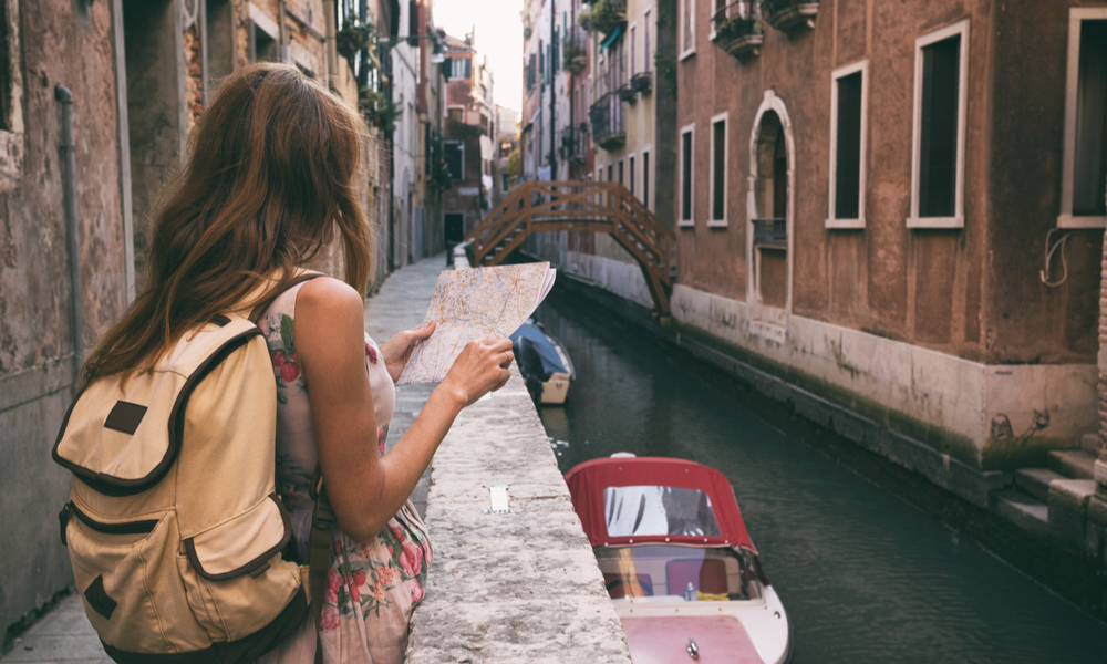 traveler girl looks at the map of walking in Venice, Italy