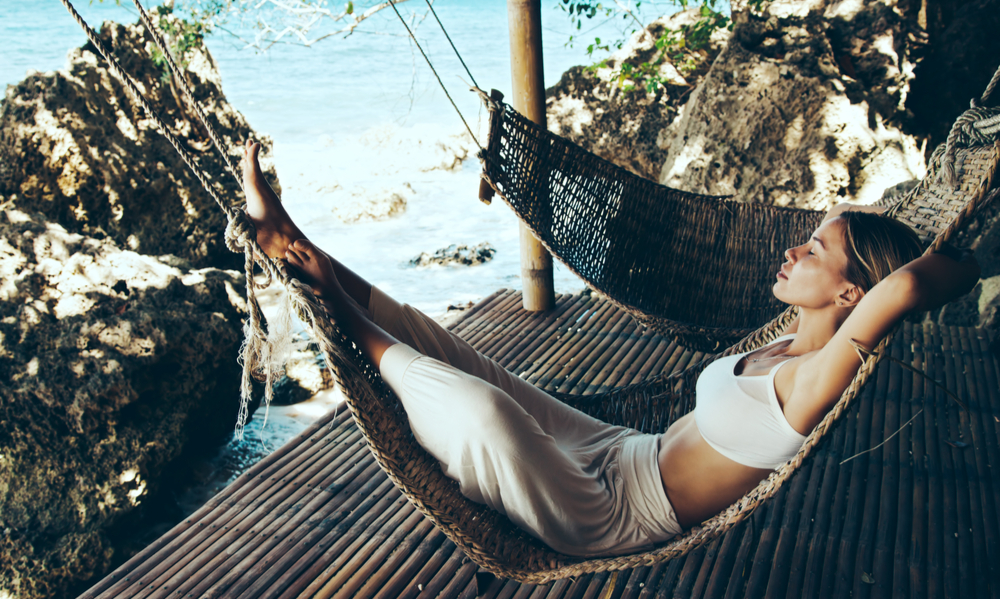 Woman relaxing in the hammock on tropical beach, hot sunny day