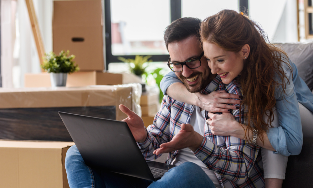 Thanksgiving Travel Myths: couple on laptop happy after finding flight deals for Thanksgiving