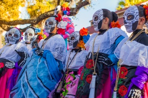 The Best Places to Celebrate Day of the Dead in the US: Group of unrecognizable women wearing traditional sugar skull masks and costumes for Dia de los Muertos celebration