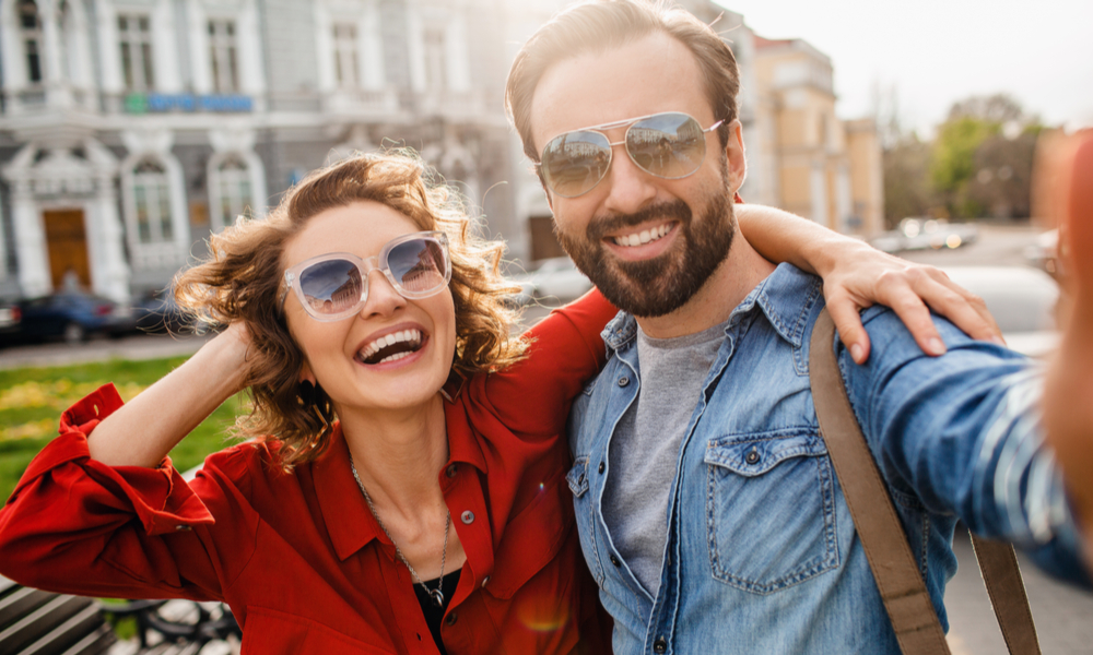How to overcome jet lag: attractive smiling man and woman traveling together, wearing sunglasses