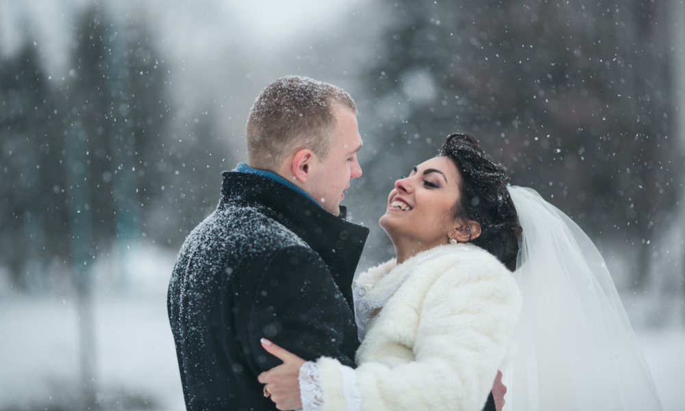 "7 Winter Wedding Ideas That Will Help You Find the Perfect Spot to Say ""I Do"": bride and groom in a winter frost with a snowflow"