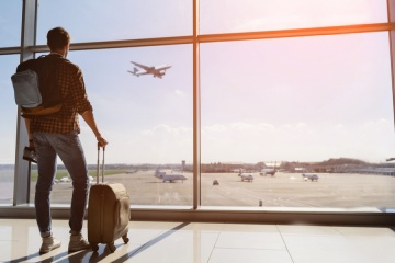 Thanksgiving Travel Myths: male tourist is standing in airport and looking at aircraft flight through window.