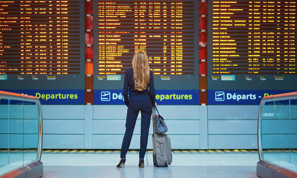 Thanksgiving Travel Myths: woman with hand luggage in international airport terminal, looking at information board, checking her flight.