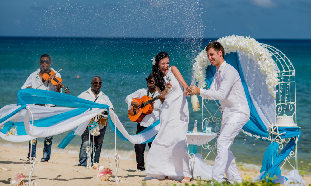 "7 Winter Wedding Ideas That Will Help You Find the Perfect Spot to Say ""I Do"": Bride and groom are opening a champagne at a wedding ceremony with three musicians near caribbean coastline"