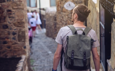 How to stay safe abroad: Man traveler with backpack explore the village walking on the old streets and explore the castles and fortresses.