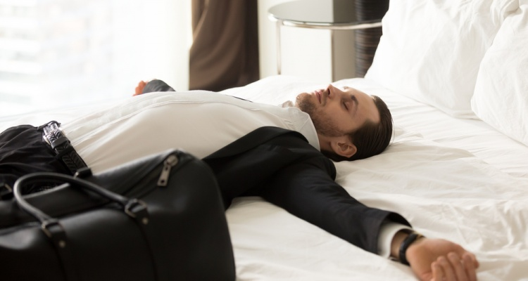 How to overcome jet lag: Exhausted young businessman laying with outstretched arms on bed next to small suitcase in hotel room