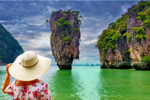 best pl;aces to travel solo in your 40s: Woman tourist with hat and floral dress looking at James Bond island in Thailand