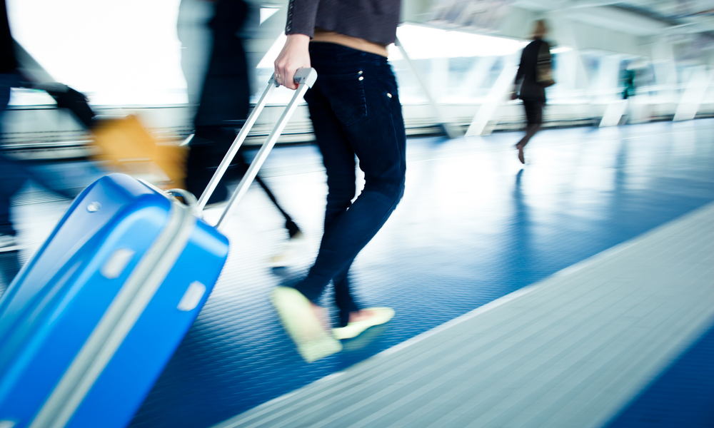 Airport rush: people with their suitcases walking along a corridor