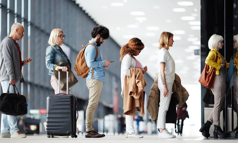 tsa travel tips to get through airport security faster: Side view of multiracial people standing in line for airport security check