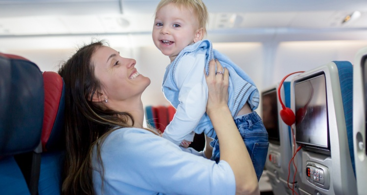 How to prepare for flying with a toddler: Mother, entertaining little toddler boy on board of aircraft on a long distance international flight, while traveling to a holiday