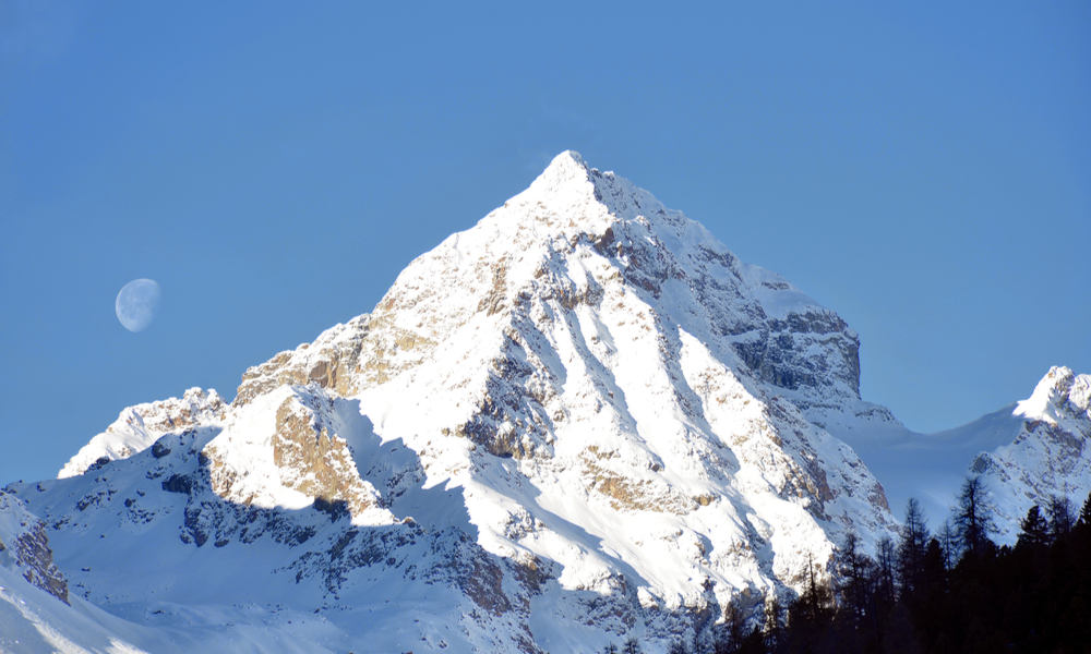 The Best Ski Towns That Also Have Beautiful Landscapes:Alp mountain with moon in St Moritz, Switzerland