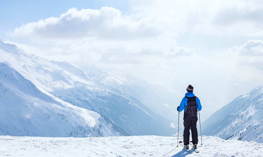 Best Places to Learn to Ski in the US: skiing background, skier in beautiful mountain landscape, winter holidays in Alps