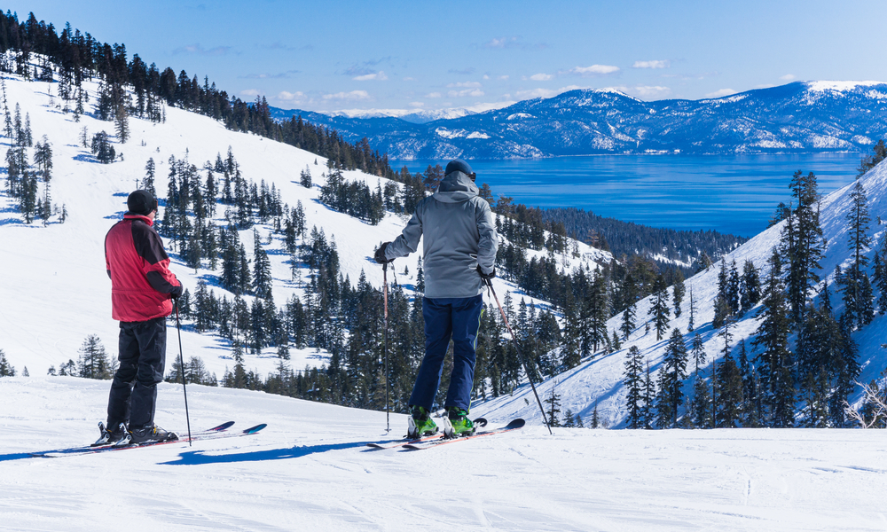 Two middle aged men on skis look out over the lake tahoe mountains