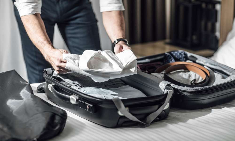 tsa travel tips to get through airport security faster: Hands of unrecognisable businessman packing his shirts in suitcase for business travel