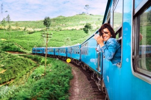 fun places to go visit in 2020: Happy smiling woman looks out from window traveling by train on most picturesque train road in Sri Lanka